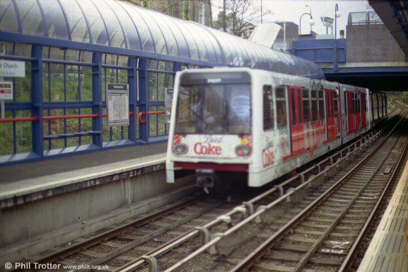 A DLR B90 car in advertising livery at Bow Church.