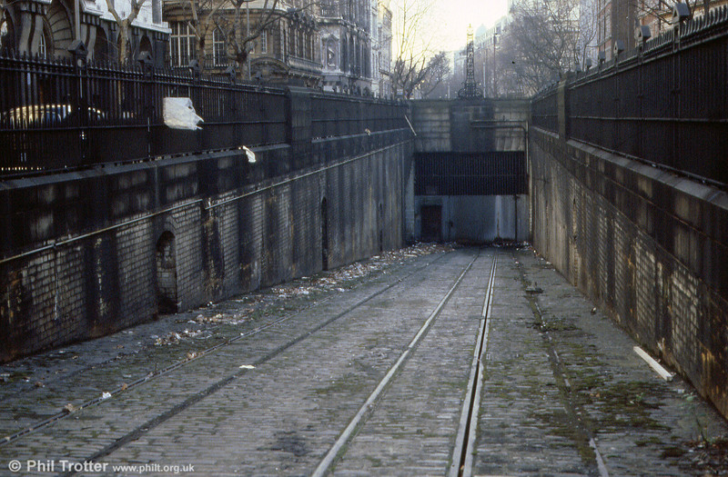 A significant remnant of London's tramway network can be seen at the Holborn end of the Kingsway Tramway Subway, where the tracks and conduit channel remain. Opened in 1906 and enlarged to take double deck trams in 1930, the subway linked the tram networks of north and south London. The subway closed on 5th April 1952, seeing occasional use after that as trams were sent south for withdrawal. The structure is now grade II listed and was photographed in 1989.