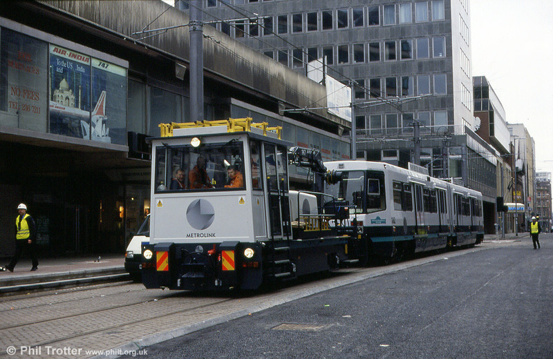 Metrolink's ancillary vehicle, the SPV, towing car 1002 'Manchester Arndale Voyager' through central Manchester on 24th November 1991.