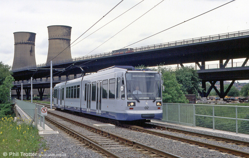 The elevated M1 and the cooling towers of Blackburn Meadows Power Station provide a backdrop to car 02 at Tinsley on 4th June 1994.