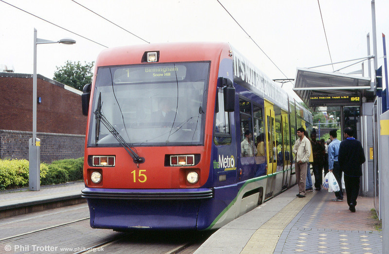 Passengers prepare to board Midland Metro car 15 at West Bromwich Central on 5th June 2004. These cars have a seating capacity of 56 plus 102 standing.