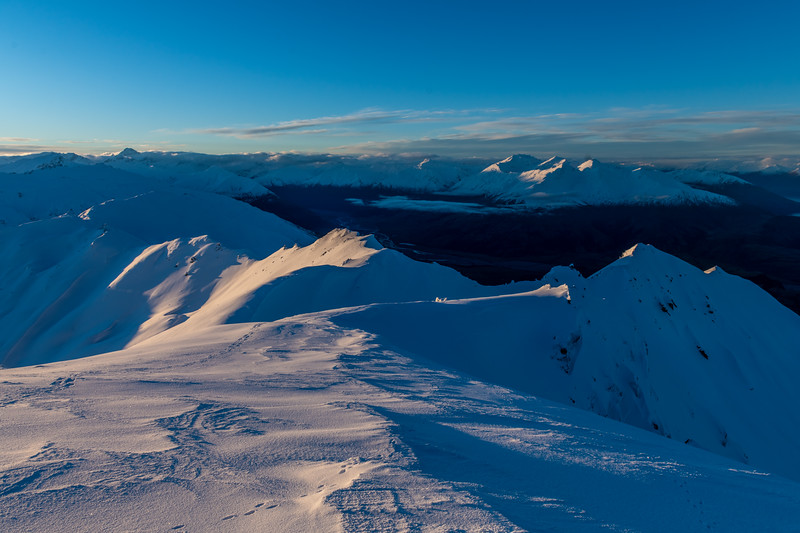 On the summit of End Peak at sunset, looking back along the ridge to Treble Cone. Mount Aspiring is on the skyline on the far left; Mount Alta and the Buchanan Peaks are on the right.