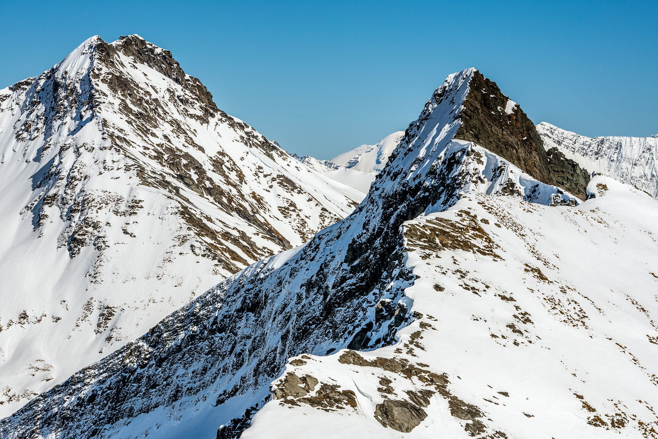 The unclimbed east ridge of Sharks Tooth Peak, facing the photographer at centre image. The south face (in the shade on the left) is also unclimbed. Craigroyston Peak behind