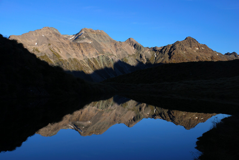 The Bryneira Range reflects in a tarn on Park Pass