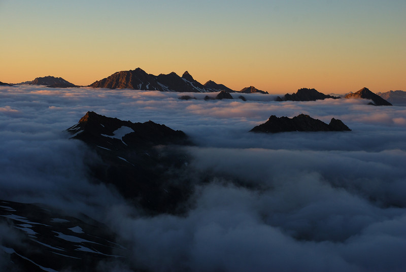 Mountain tops like islands in an ocean of cloud. View at sunrise from Mt Tyndall's west ridge