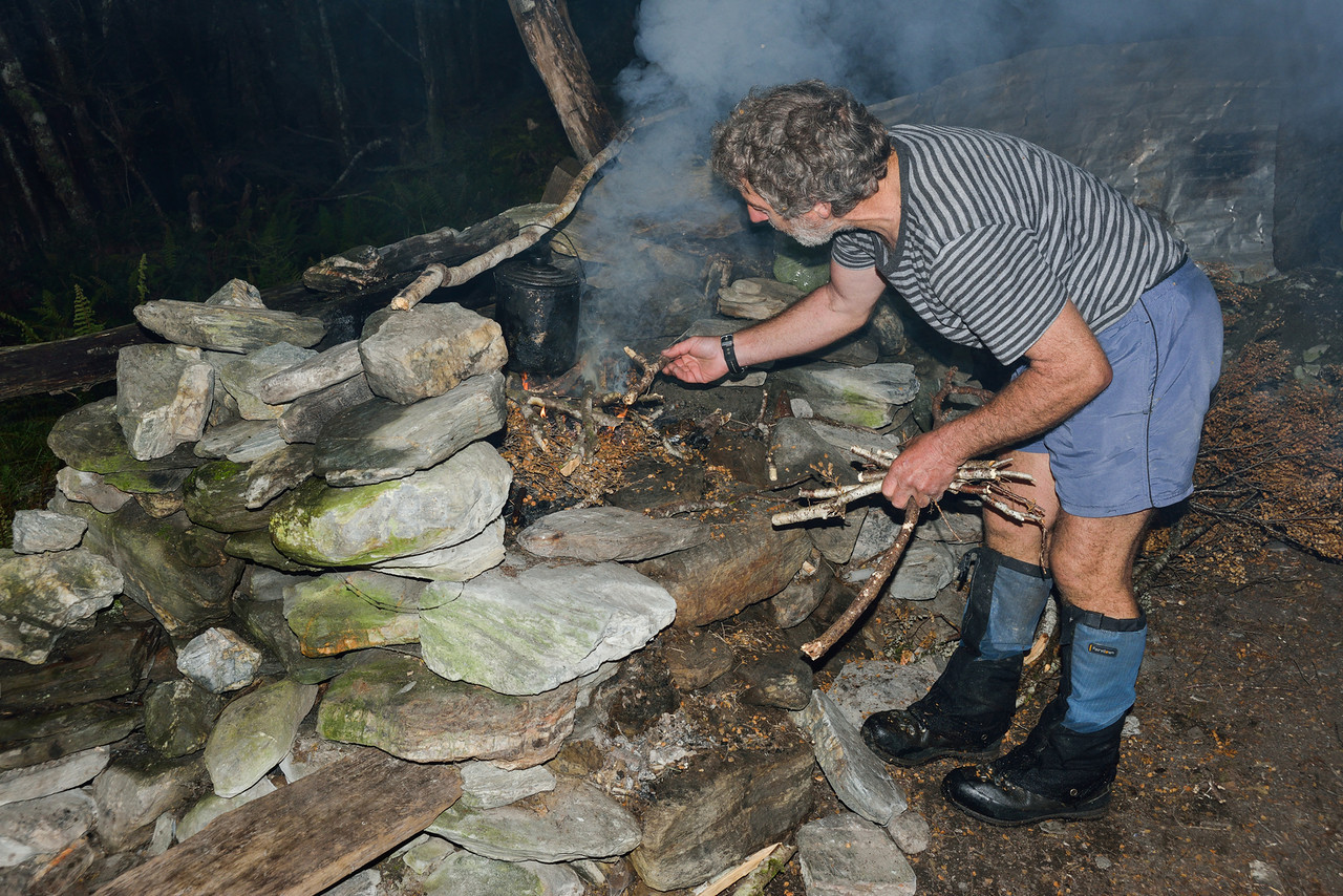 Lighting a fire in the rock bivvy at Cattle Flat, Dart Valley