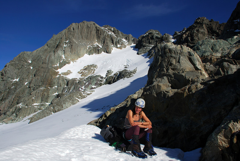 Taking a rest at the bottom of the final snow field on Somnus. At the top, our route follows the system of snowy ramps and ledges climbing diagonally to the left.