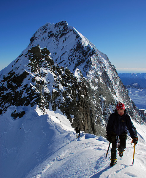 Nina on the summit ridge of Popes Nose. The Coxcomb ridge of Mt Aspiring behind.