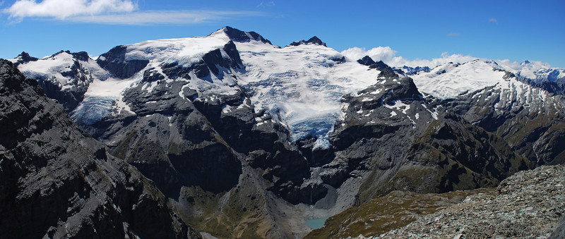 View into Hunter Creek West Branch from the north-east ridge of O'Leary Peak. From left to right are Head Peak, Mt Head, Moira Peak, OSONZAC Twins and Mt Clarke. Mt Edward and Mt Aspiring are visible in the back on the far right.