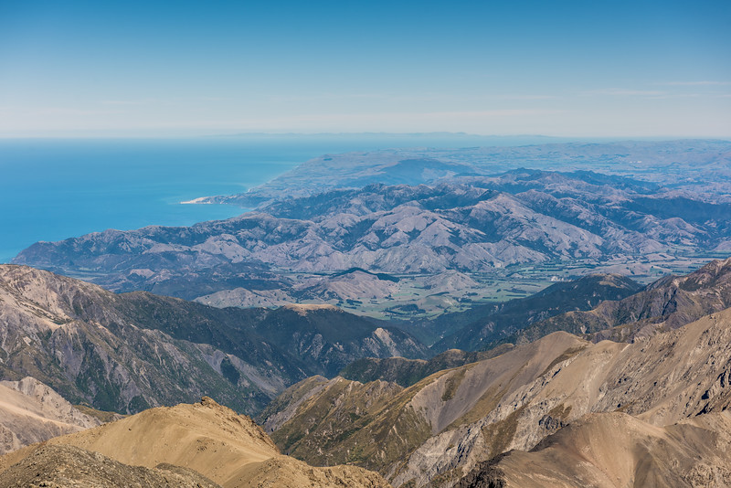 View south-west along the east coast of the South Island from the summit of Manakau. Banks Peninsula is just visible on the skyline at centre image.