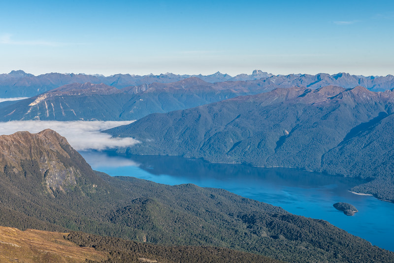 View across Lake Te Anau from Mount Eglinton. The most prominent peaks on the skyline are Mt Lyall (far left), Coronation Peak and Mount Irene (centre image).
