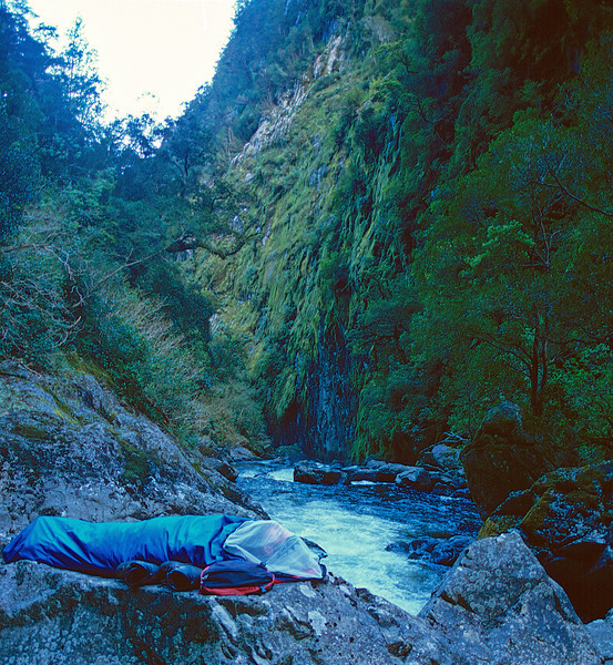 Alex perched in his bivvy bag on a square boulder at the edge of the river