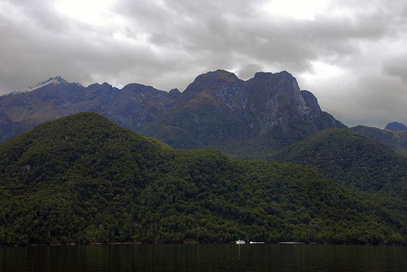 The Milford Track boat in front of Foliage Head, Lake Te Anau. Skelmorlie Peak top left