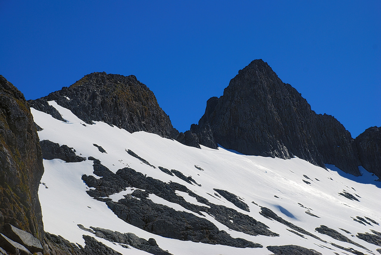 Nicholas Peaks (pt 1792m) from the shelves above the bluffs at the head of the Castle River. The saddle at centre image is the crux on the route around Lake Quill