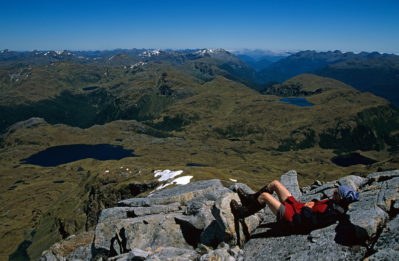 Sun-bathing on unnamed peak 1595m south-east of Tamatea Peak, Merrie Range. Lake Roe and Lake Horizon below.