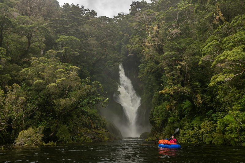 Pack-rafting on Lake Thomson, at the toe of the waterfall draining Lake Wade. George Sound Route, Fiordland National Park.