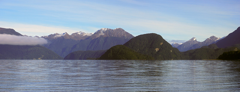 View across Lake Manapouri from Moturau Hut. Rona Island and the Behive at centre image, in front of Precipice Peak. Leaning Peak and Steep Peak are on the right