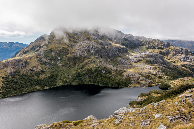 Large unnamed lake (Pt 761m) west of Rugged Mount. Unnamed Peak Pt 1310m is in cloud above.