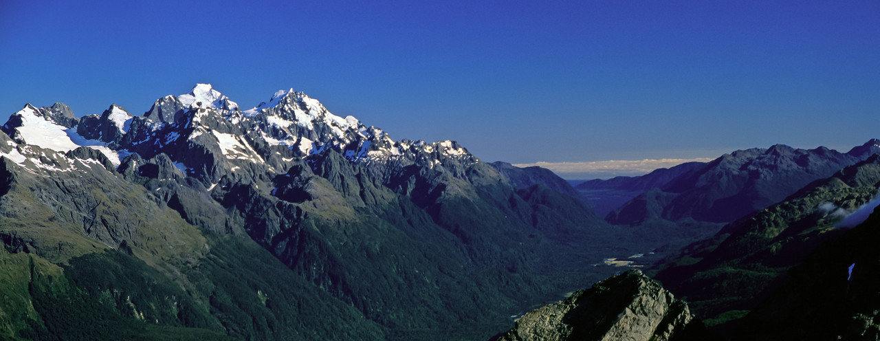 Darran Mountains and Hollyford River from Unnamed Peak 1777m. From left to right are Mount Revelation, Karetai Peak, Taiaroa Peak, Mount Te Wera, Mount Tutoko, Mount Madeline