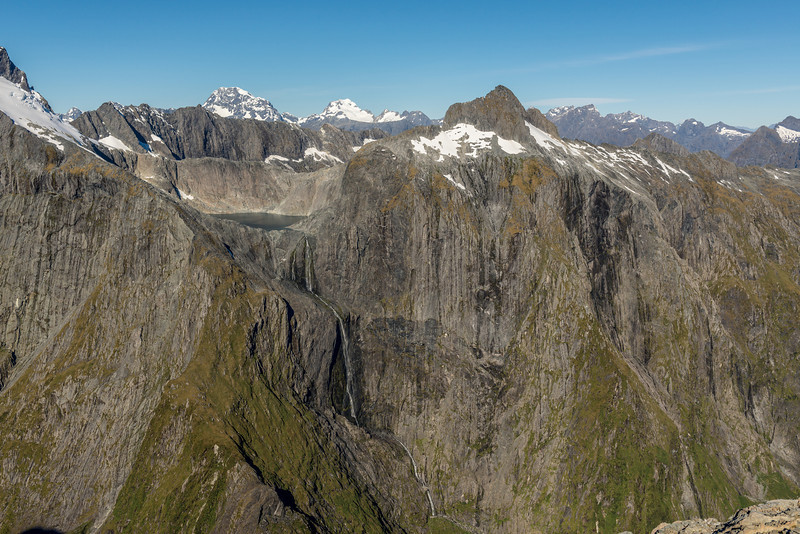 View across Poseidon Creek from Pt 1632m: Lake Terror, Terror Falls and Terror Peak. Mount Tutoko and Mount Madeline stand out in the background. The sheer faces of Terror Peak are one of the biggest unclimbed challenges in the country