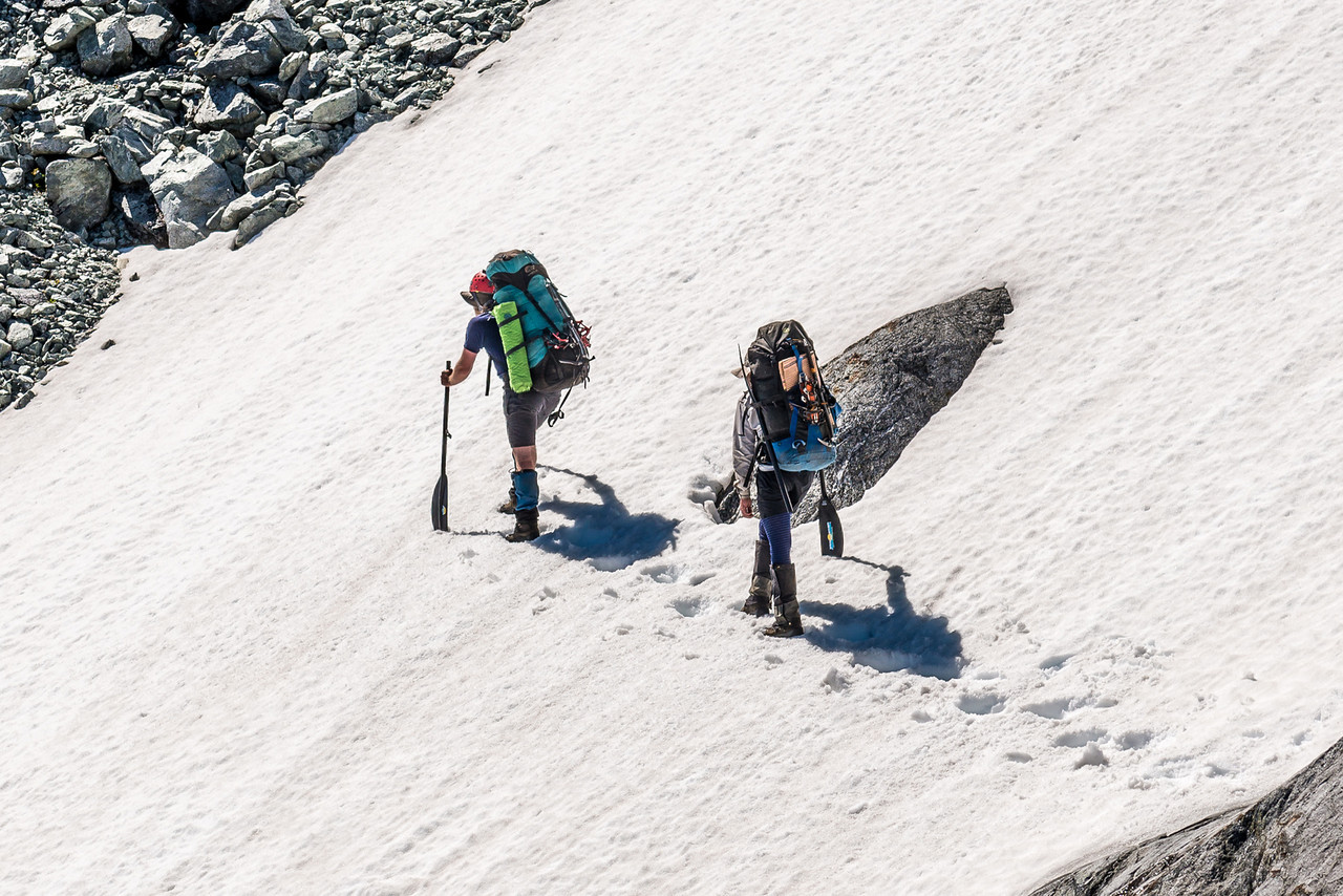 Max and James crossing a snow field on the tops between MacKay Creek and Poseidon Creek. And who needs an ice-axe when you can have a paddle?