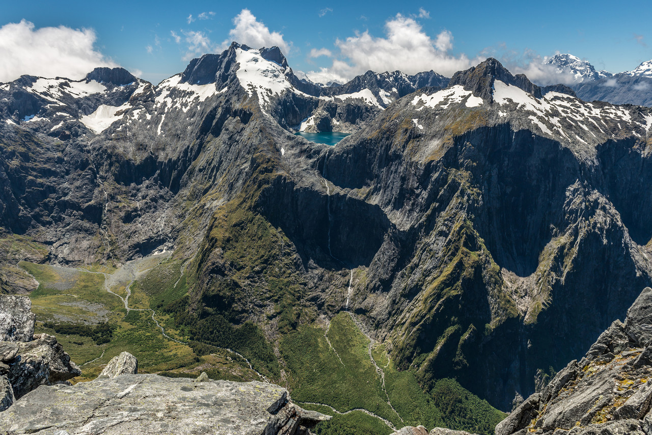 "View into the head of Poseidon Creek from ""The Watchtower"" (Pt 1674m). From left to right are the Llawrenny Peaks, Lake Terror, Terror Peak, Mount Tutoko. The sheer faces of Terror Peak are one of the biggest unclimbed challenges in New Zealand."