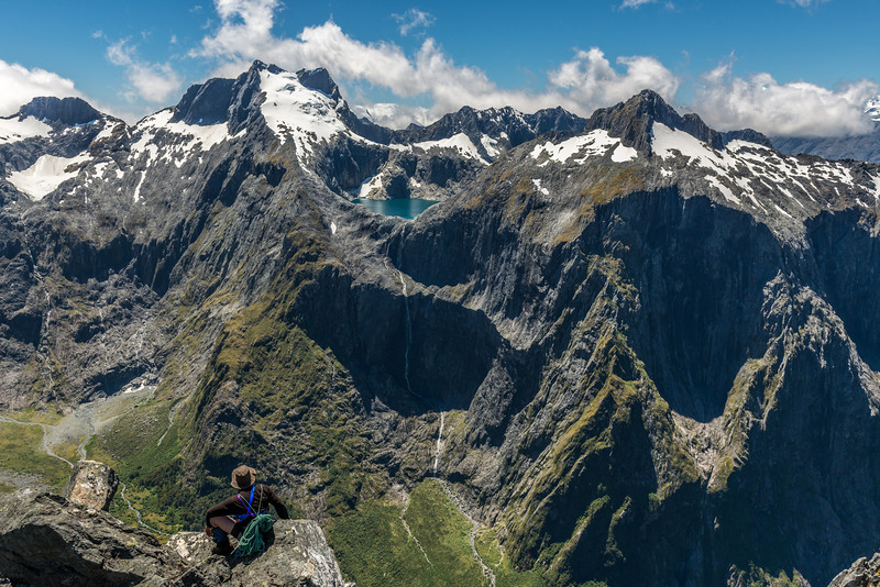 """Max on the summit of """"The Watchtower"""" (Pt 1674m), looking at the Lawrenny Peaks and Terror Peak across Poseidon Creek. The highest waterfall in New Zealand (750m high) drains Lake Terror at centre image"""