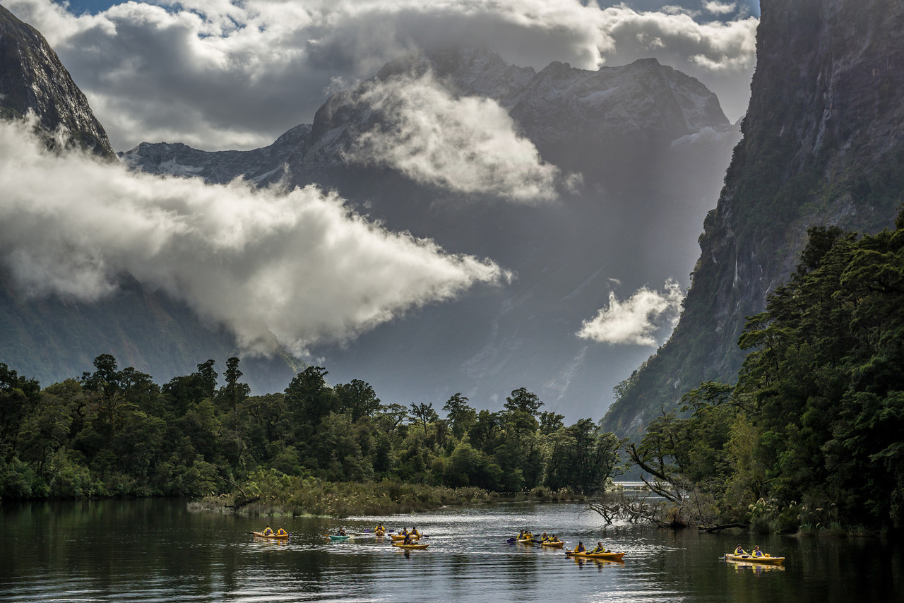 A guided group paddling to Sandfly Point, Milford Sound. Mount Underwood is in cloud at centre image