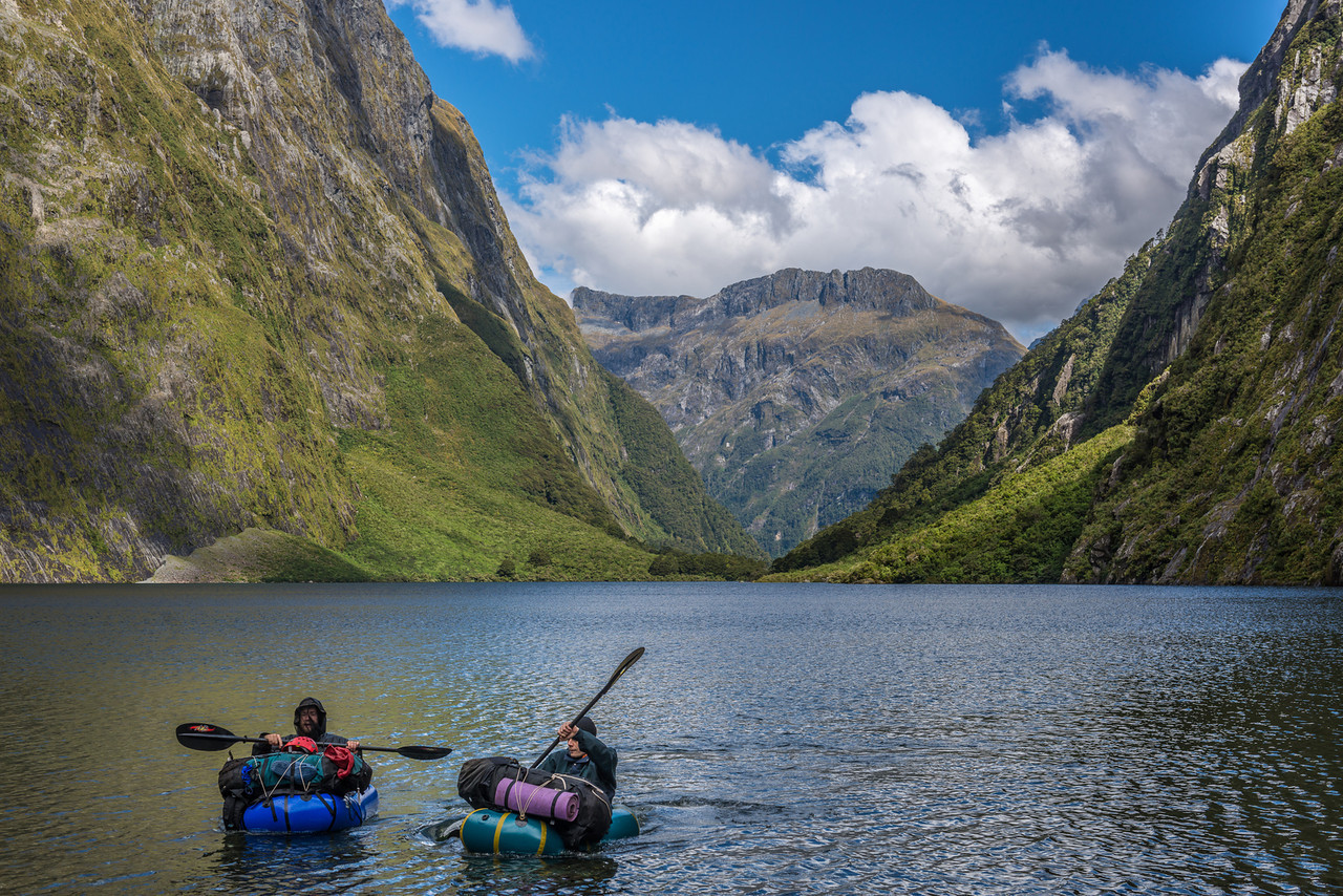 Peter and Max paddling across the MacKay Lake. Surrounded by sheer bluffs on both sides, there is no practical route around it. The flat ridge above Boatshed Hut in the Arthur River is at centre Image