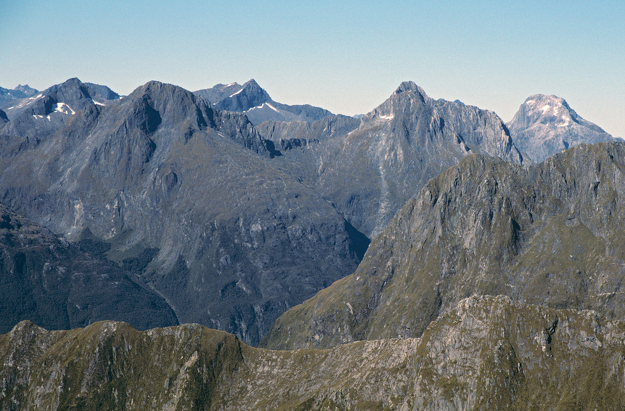 View from the summit of Mitre Peak. The Sheerdown Hills raise above Mt Philipps and Devils Armchair. On the horizon from left to right: Access Peak (back), Odissey Peak (front), Lloyd Peak (back), Mt Ada (front), Mt Mitchelson (back)