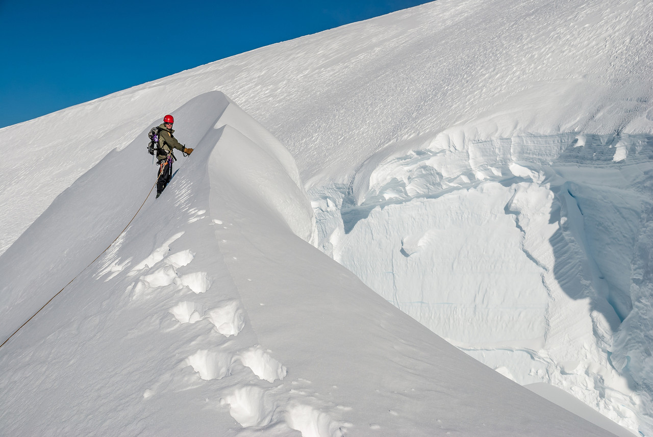 An ice flake bridges a massive crevasse near the top of Mount Tutoko's south face