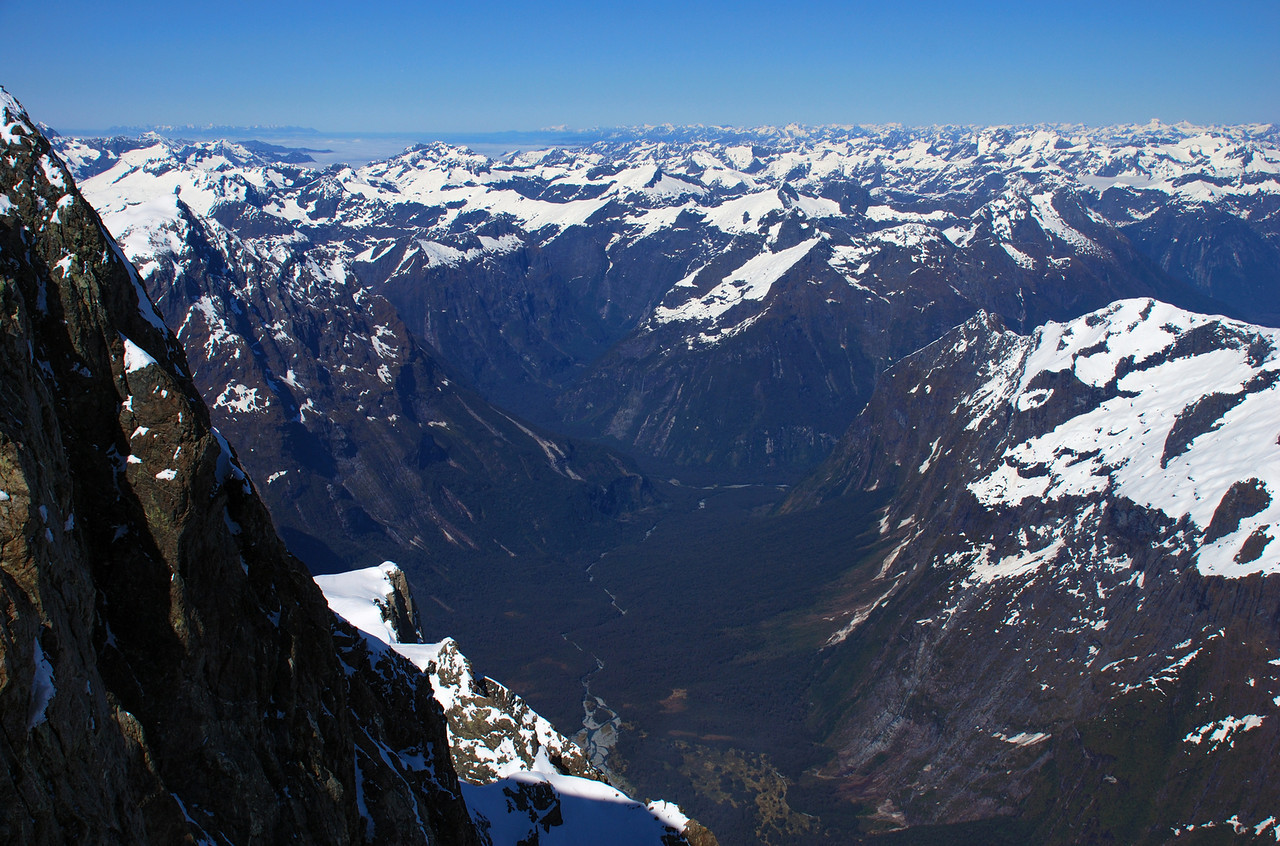View into the Tutoko Valley from the summit ridge of Mount Tutoko. The Takitimu Mountains are on the far left horizon, Mount Titiroa just left of centre image, Mount Irene and Coronation Peak on the far right