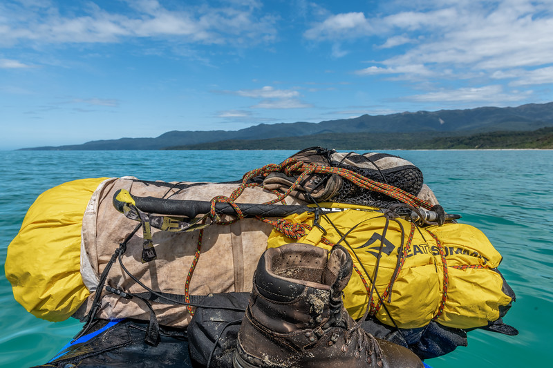 A packraft laden with three weeks worth of food and gear on Te Waeway Bay, heading to Port Craig.