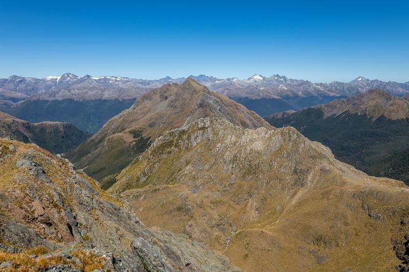 Pt 1620m, Skippers Range. On the skyline from left to right are the Olivine Range, Forbes Mountains, Niobe Peak and Poseidon Peak, Somnus. Fiordland National Park.