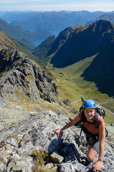 Gwenn scrambling on the summit ridge of Triton Peak. The Glade Burn and Lake Te Anau behind