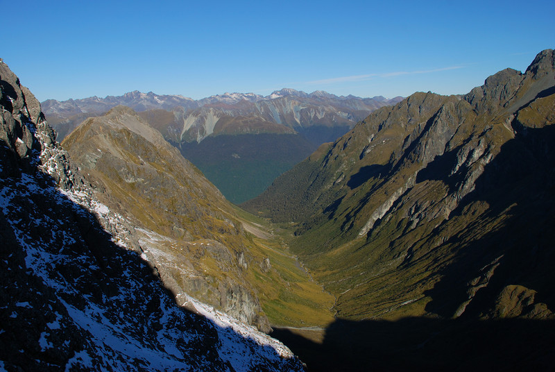 Looking down Waterfall Creek from the south ridge of Triton Peak. The Livingstone Mountains are on the horizon. The most prominent elevations are the David Peaks (left) and Moffat Peak (centre right)