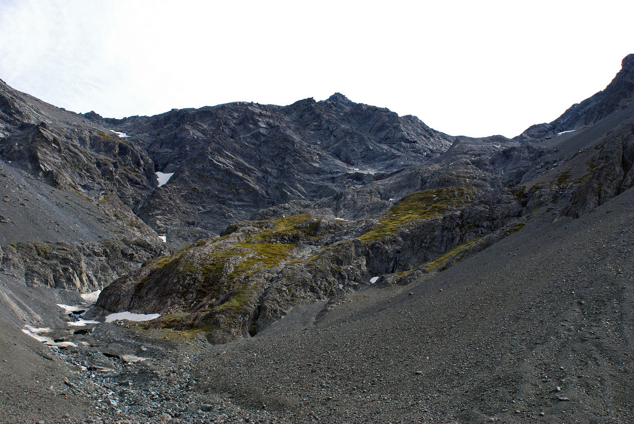 Jamieson Stream valley head. The snow couloir ends near the left edge of the image. Safer alternative routes descend the slope on the true left of the couloir, with possible exits via the snow grass ramp at the lowest point of the bluffs (just left of centre image), or the scree gully near the right edge of the image.