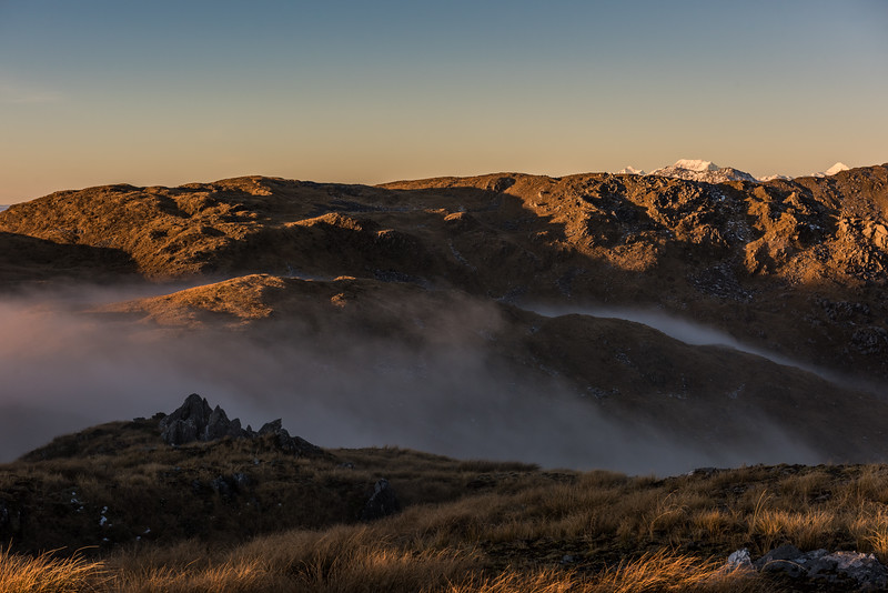 Fog rolls over the Mataketake Range tops at sunset. Mount Tasman, Aoraki/Mount Cook and Mount Sefton are just visible on the skyline.
