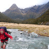 Nina crosses the stream draining Iceland - and so our boots get wet