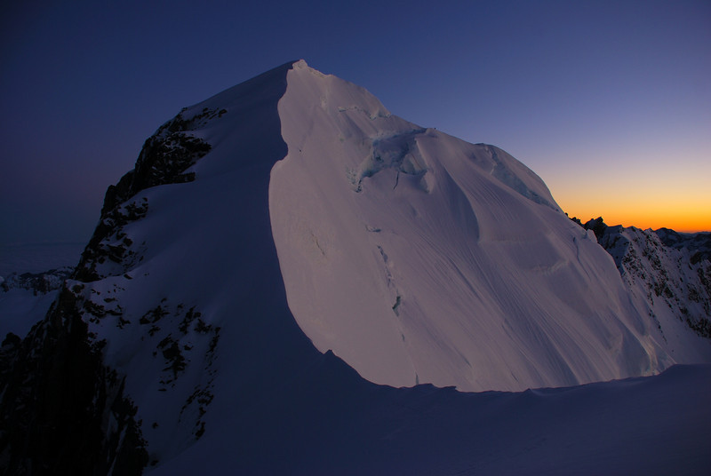 Lendenfeld Peak from Engineer Col at dawn. We climbed Lendenfeld at night, then descended the elegant snowy ridge at centre image. Jaz and Tiff are just  visible on the skyline ridge
