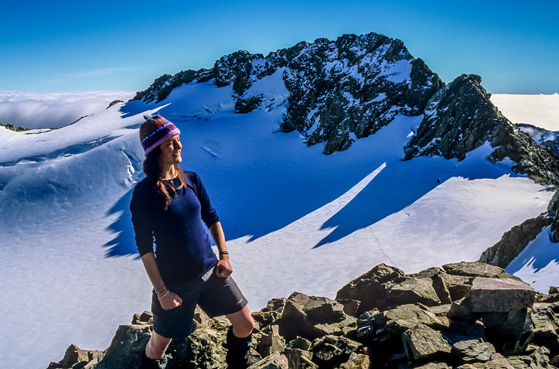 Erin on Mount Rolleston's Low Peak. High and Middle Peaks rise above the Crow Glacier in the back