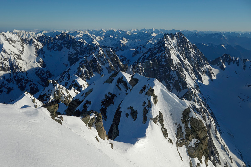 View north from Mt Arrowsmith. The most prominent peaks are, from left to right, Red Peak (on left edge), North Peak (dark, rocky), Coulouir Peak (small, just left of centre image) and Jagged Peak