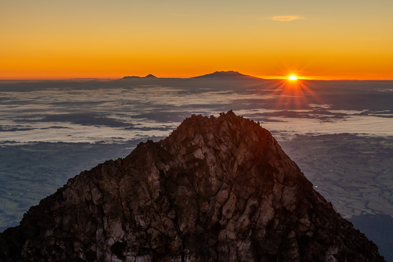 Sharks Tooth (front), Ngauruhoe and Ruapehu (back) from the summit of Taranaki at sunrise.