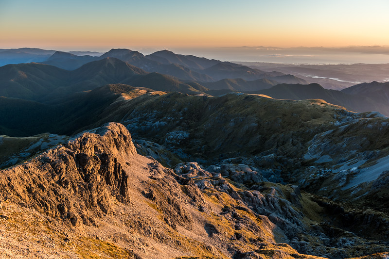 View into Horseshoe Basin and Tasman Bay from Mount Arthur at sunrise.