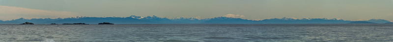 The coast and mountains of Fiordland from Smoky Beach. Bishop and Clerks Islands in the foreground