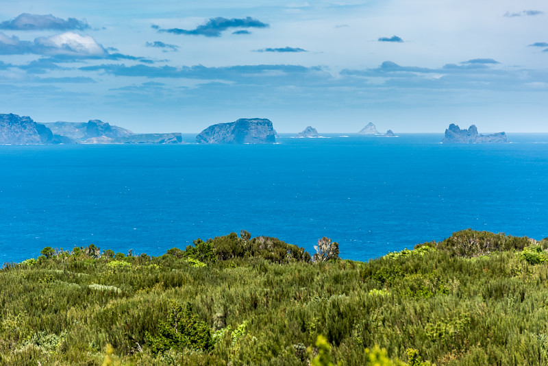 View south from Rangaika, Chatham Island. From left to right are Mangere Island (with Pitt Island in the background), Little Mangere Island, Unnamed island Pt 134m, The Pyramid, South Reef, The Castle.