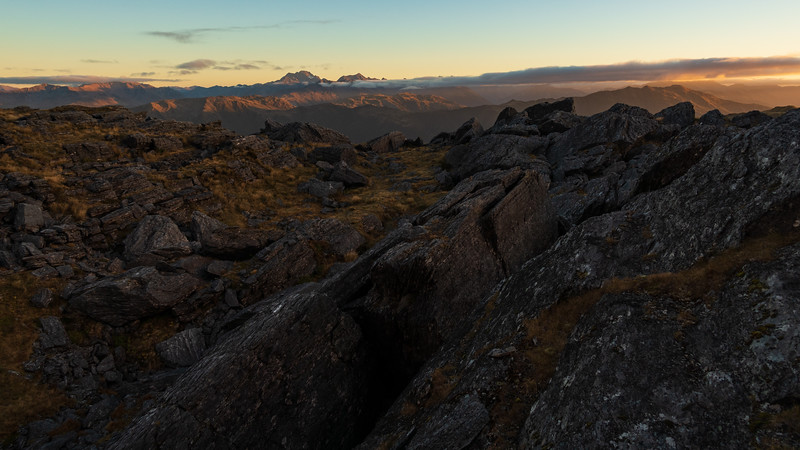 Schist boulders near camp, Rolleson and Armstrong in the distance.