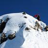 Dave downclimbing the step on the summit ridge.