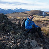 Jeremy sheltering from the wind on the summit of Ben More, Torlesse Range behind.
