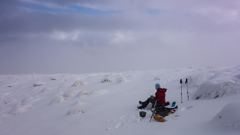 A sheltered spot for a lunch brew below the summit. Hutt Range poking through the cloud.